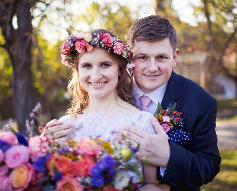 nevěsta se svatebním věnečkem a svatební kyticí v lučním stylu se ženichem s koršáží